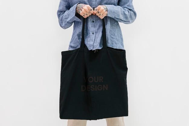 Mulher tatuada em uma camisa de linho azul segurando uma maquete de bolsa preta