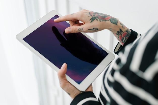 Mulher tatuada usando um tablet