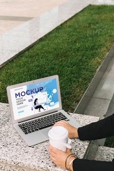 Mulher trabalhando ao ar livre com maquete de laptop