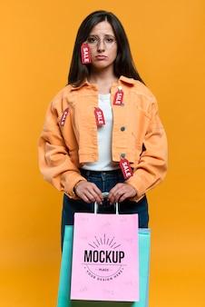 Mulher triste segurando um modelo de sacola de compras