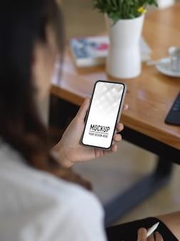 Mulher usando maquete de smartphone enquanto está sentada no local de trabalho