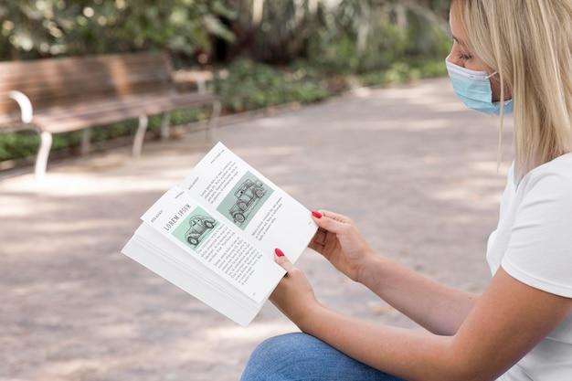 Mulher usando máscara lendo livro de rua