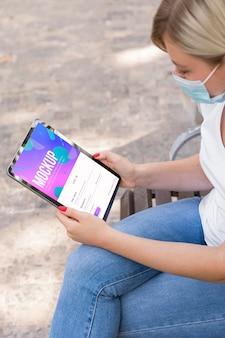 Mulher usando máscara na rua lendo livro no tablet