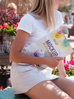 Mulher vestida casual, segurando uma revista mock up