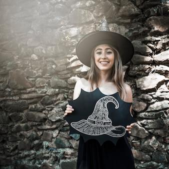 Mulher vestida como uma bruxa segurando um desenho de um chapéu