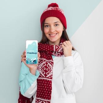 Mulher vestindo um moletom e segurando uma maquete de telefone