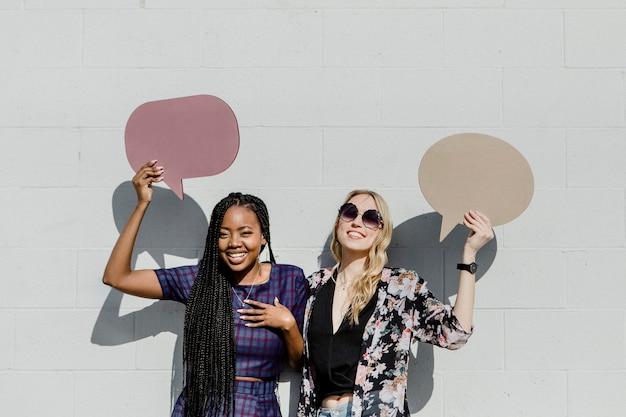 Mulheres alegres mostrando balões de fala em branco