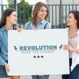 Mulheres segurando modelo de placa