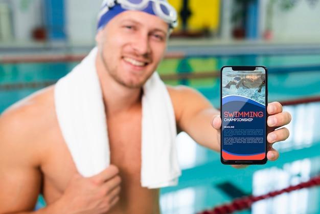Nadador em uma casa na piscina, segurando um telefone móvel de mock-up
