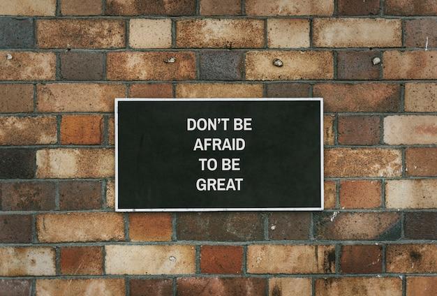 Não tenha medo de ser grande maquete da placa em uma parede de tijolos