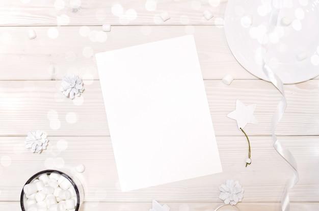 Natal com maquete de cartão e decorações brancas na mesa de madeira