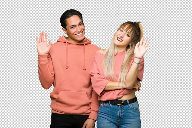No dia dos namorados jovem casal saudando com a mão com expressão feliz