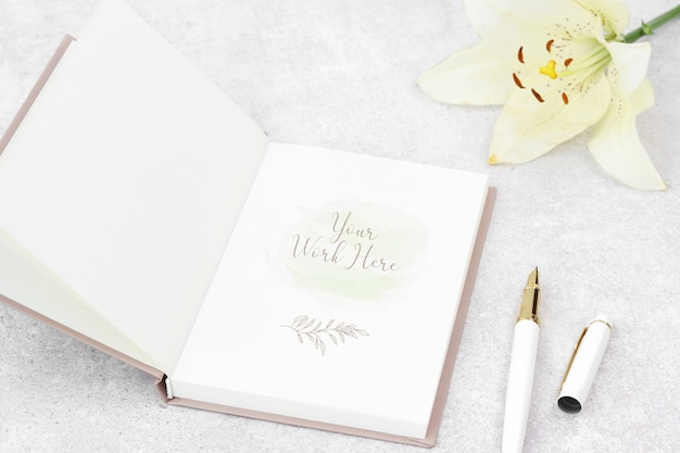 Notas de maquete com lírio e caneta branca
