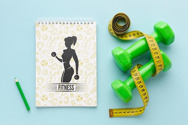 Notebook ao lado de equipamentos de fitness