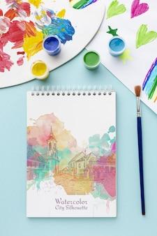 Notebook com aquarelas na mesa