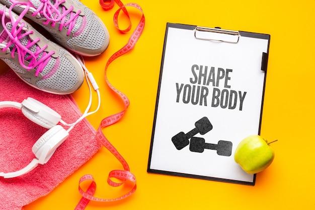 Notebook com mensagem de fitness e equipamentos