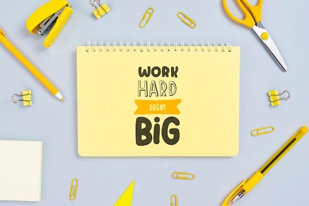 Notebook com mensagem positiva e ferramentas de escritório ao lado