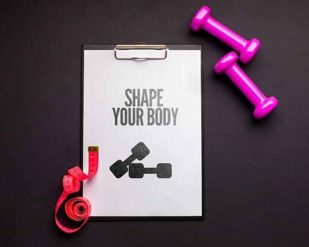 Notebook com pesos de fitness e medidor