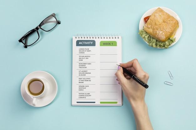 Notebook de vista superior com tarefas diárias e café