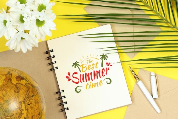 Notebook mock verão com globo, flores e folhas de palmeira