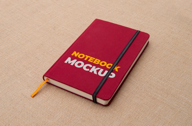 Notebook vermelho em maquete de superfície de tecido