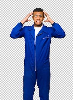 O homem afro-americano novo do trabalhador toma as mãos na cabeça porque tem a enxaqueca