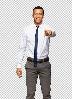O homem de negócios afro americano novo aponta o dedo em você com uma expressão confiável