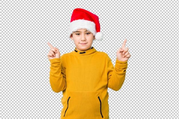 O rapaz pequeno que comemora o dia de natal que desgasta um chapéu de santa indica com ambos os dedos dianteiros que mostram acima um espaço em branco.