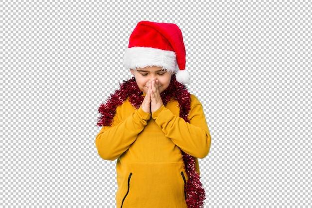O rapaz pequeno que comemora o dia de natal que veste um chapéu de santa isolado guardando as mãos reza perto da boca, sente-se confiante.