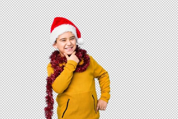 O rapaz pequeno que comemora o dia de natal que veste um chapéu de santa isolou a vista lateral com expressão duvidosa e cética.