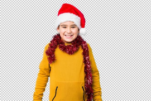 O rapaz pequeno que comemora o dia de natal que veste um chapéu de santa isolou feliz, sorrindo e alegre.