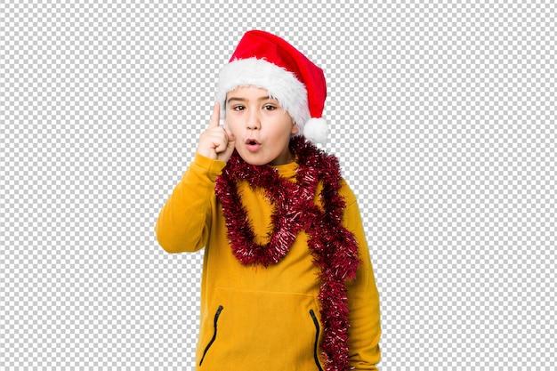 O rapaz pequeno que comemora o dia de natal que veste um chapéu de santa isolou tendo uma ideia, conceito da inspiração.