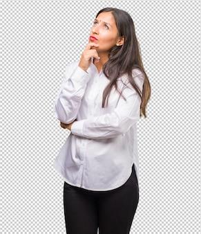 O retrato de uma jovem indiana pensando e olhando para cima, confuso com uma ideia, estaria tentando encontrar uma solução