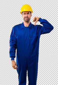O trabalhador novo com o capacete que mostra o polegar assina para baixo com expressão negativa. expressão triste
