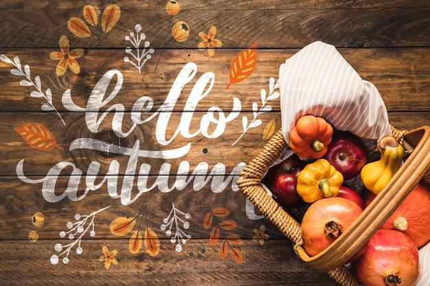 Olá outono citação com cesta de piquenique cheia de legumes