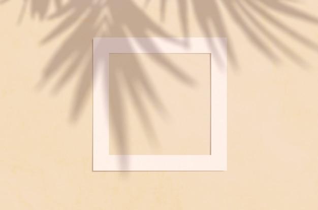 Opinião superior da configuração lisa do copyspace criativo com quadro branco de papel e sombra tropical da palma das folhas na cor bege.