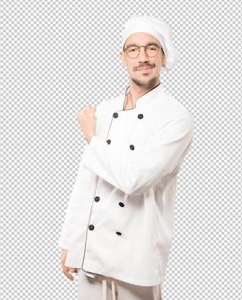 Orgulhoso jovem chef fazendo um gesto de força com o braço