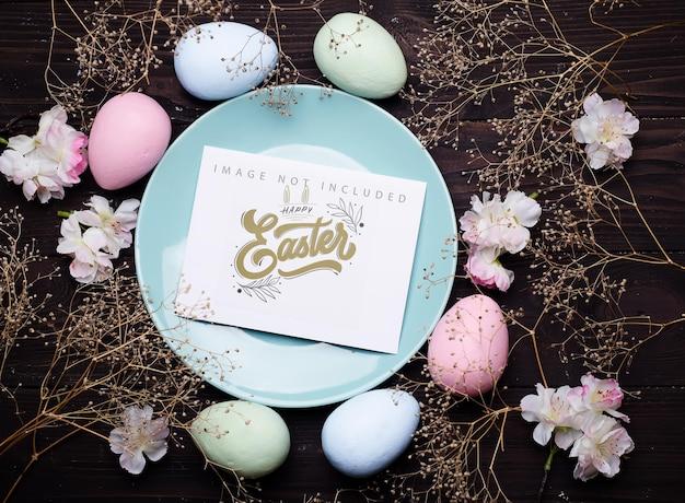 Ovos de páscoa em cor pastel em um prato com maquete de cartão