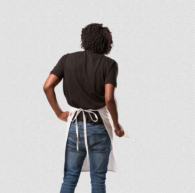 Padeiro americano africano bonito mostrando volta, posando e esperando, olhando para trás