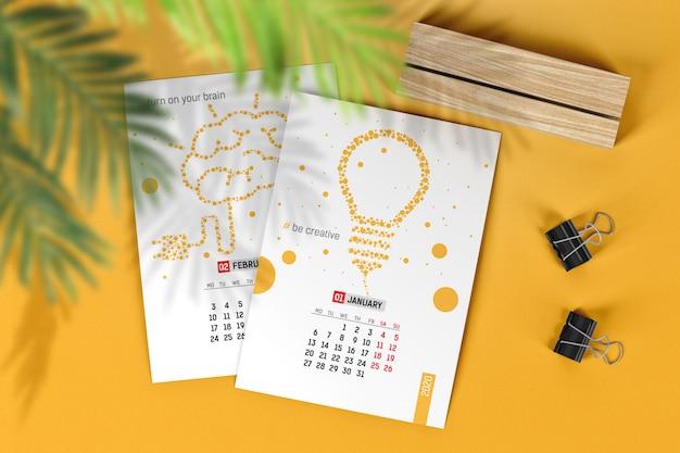 Páginas de calendário vertical com maquete de suporte e clipes de madeira