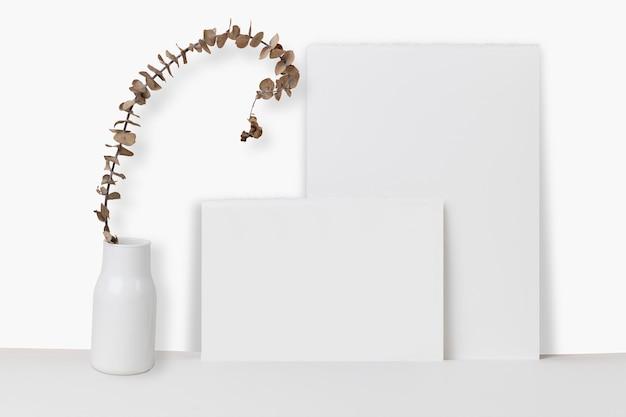 Papel apoiado em maquete psd de parede com planta seca em um vaso