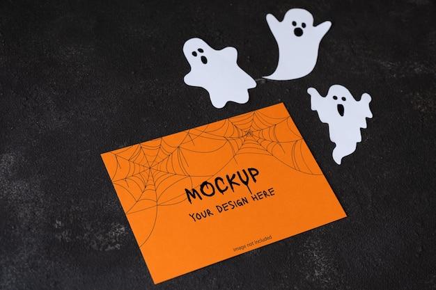 Papel em branco laranja com fantasmas fofos em fundo de concreto escuro modelo para o feriado de halloween