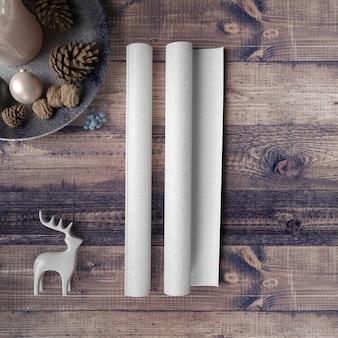 Papel em branco na mesa de madeira, rodeada por enfeites e pinheiros