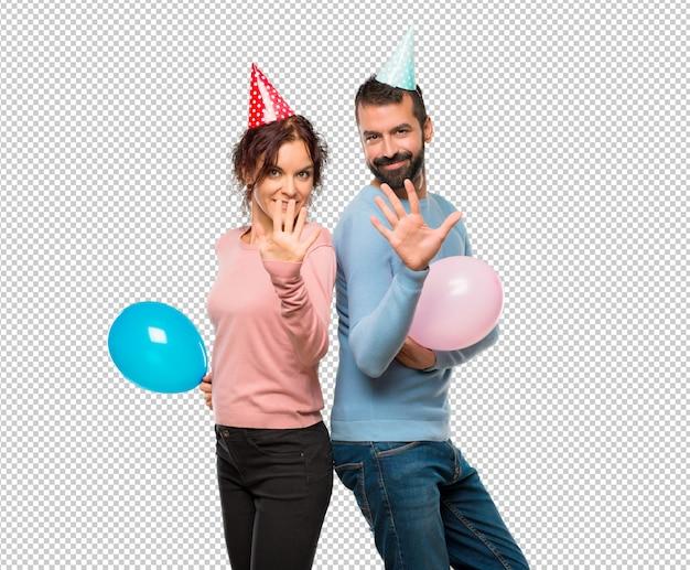 Par, com, balões, e, chapéus aniversário, contando, cinco, com, dedos