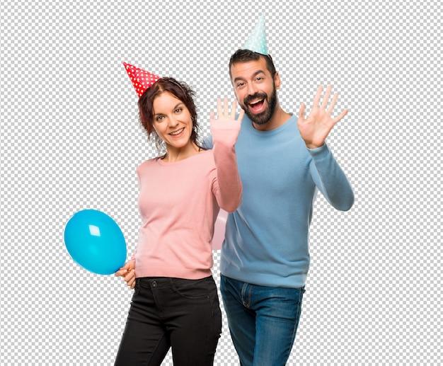 Par, com, balões, e, chapéus aniversário, saudando, com, mão, com, feliz, expressão