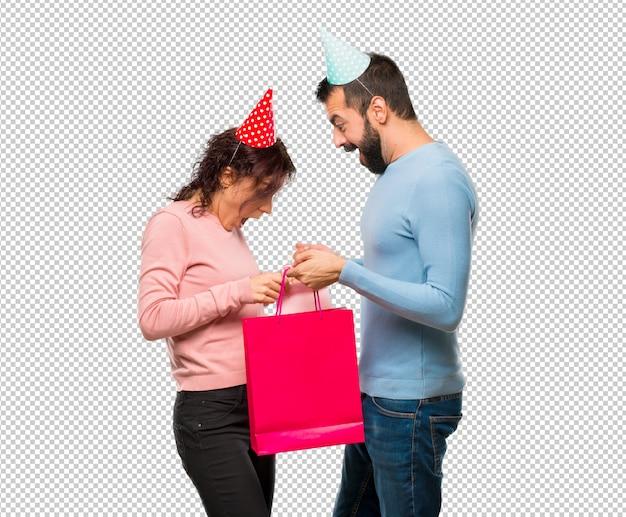 Par, com, chapéus aniversário, e, com, bolsas para compras