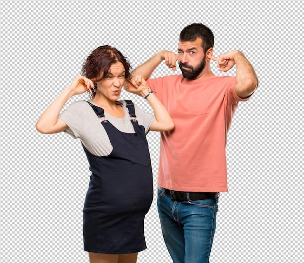 Par, com, mulher grávida, coberta, orelhas, com, mãos