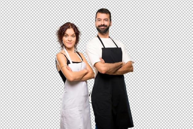 Par, cozinheiros, mantendo, braços, cruzado, lateral, posição, sorrindo