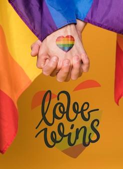 Pares de homens no amor que guardam as mãos no dia do orgulho alegre. amor vence