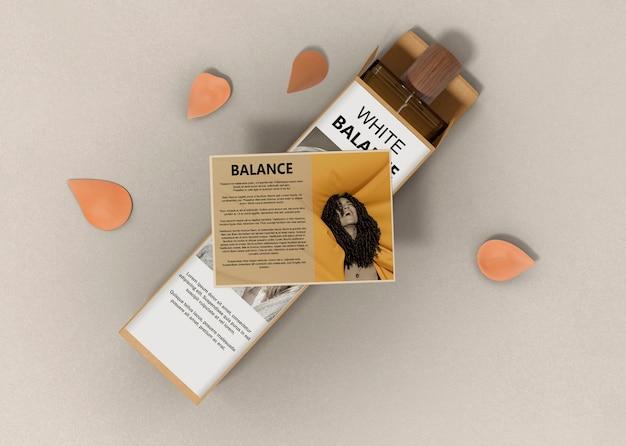 Perfume com descrição ao lado e pétalas